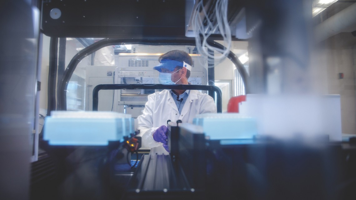 A male worker at the Cornell COVID Testing Lab, seen through stacks of samples; he is wearing a mask, a visor, and gloves