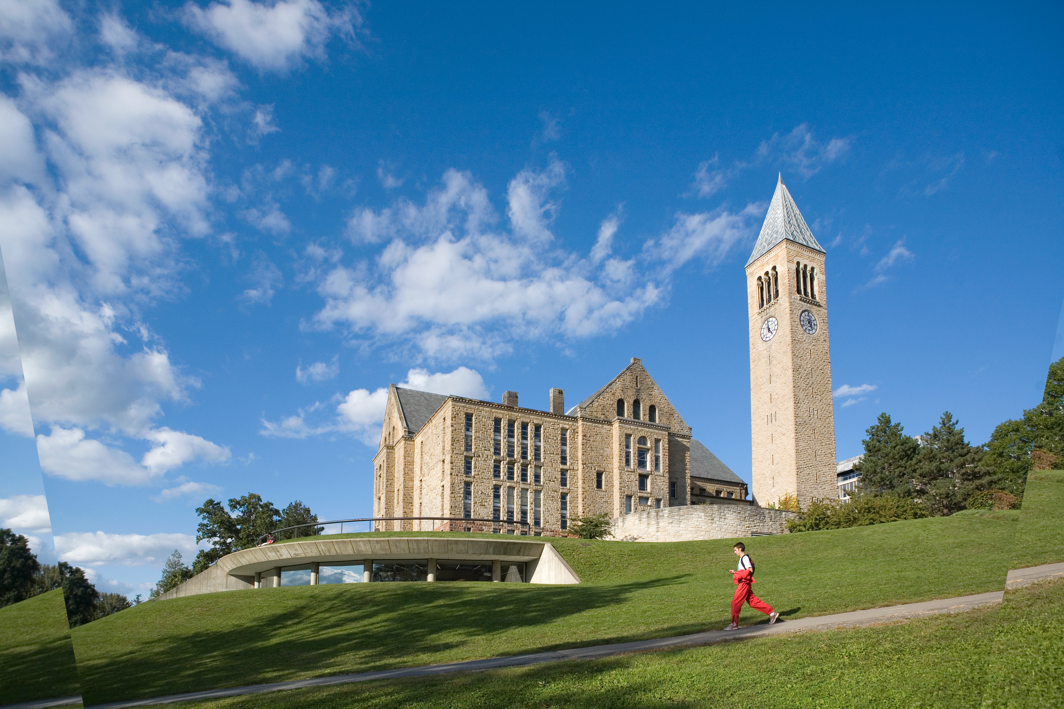 A student jogs down Libe Slope past Uris Library and McGraw Tower in summer.