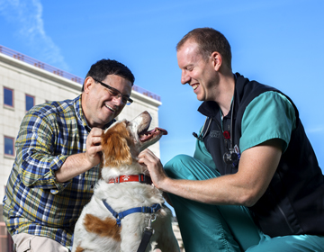 A vet and client smiling with a dog