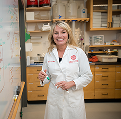 Lisa Fortier at a whiteboard in a lab coat