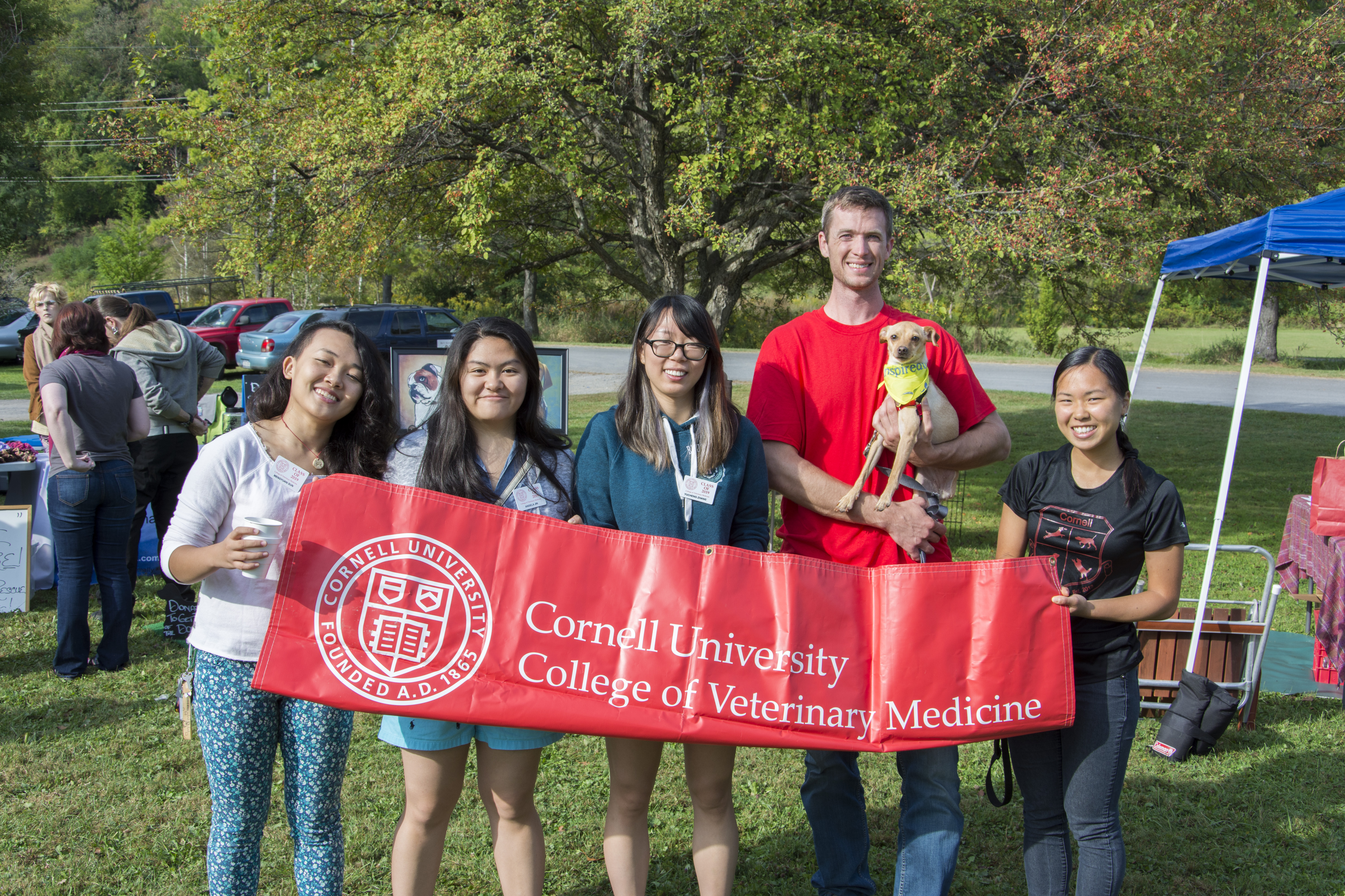 five veterinary students holding a CVM banner at a community event