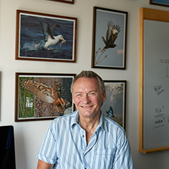 David Russell at his desk with pictures in the background