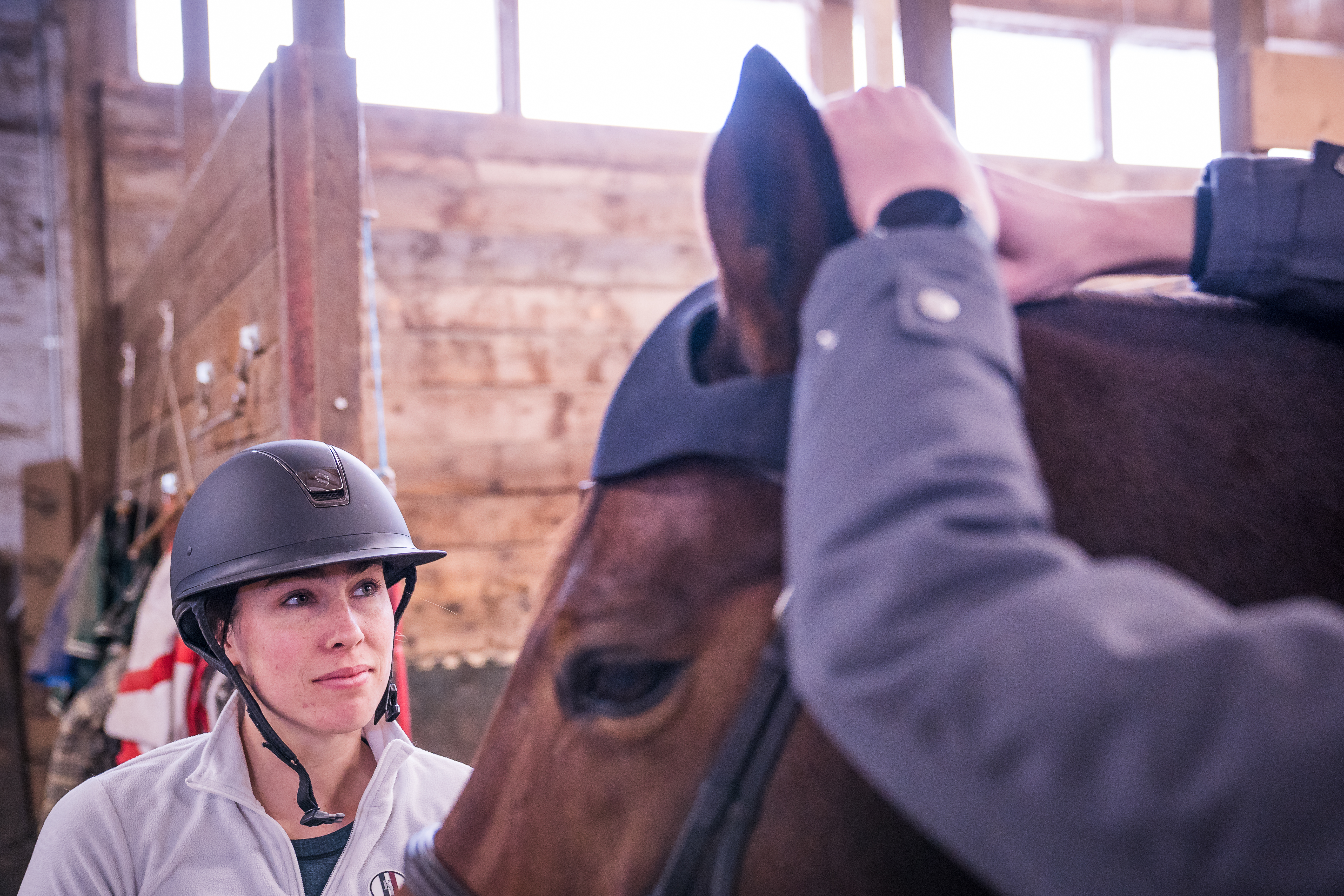 A rider looks on as a cap is placed on her horses head.