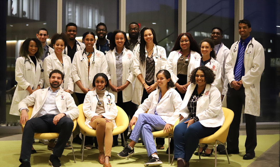 A group veterinary student of color seated and standing in the Cornell Vet atrium to mark Black History Month