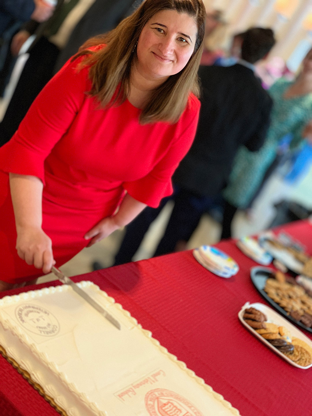 "Dr. Marta Castelhano cuts the ""accredited"" cake at the event."