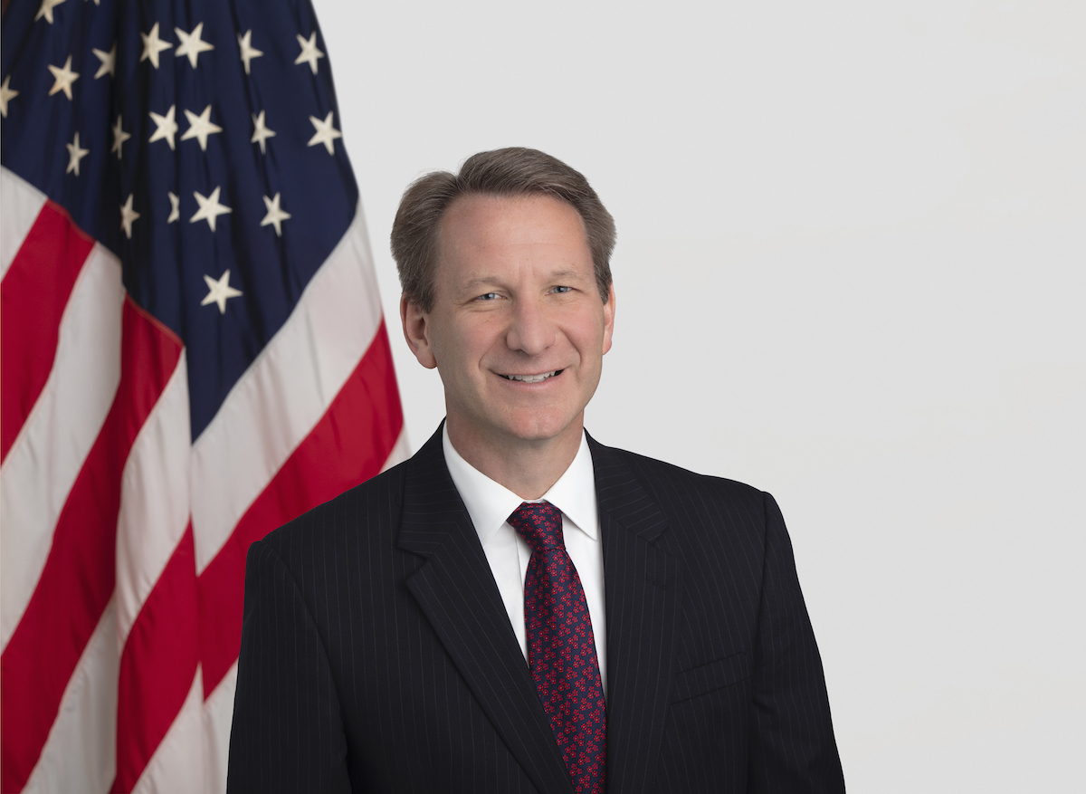 A headshot of Dr. Normal Sharpless, wearing a suit and tie with an American flag backdrop