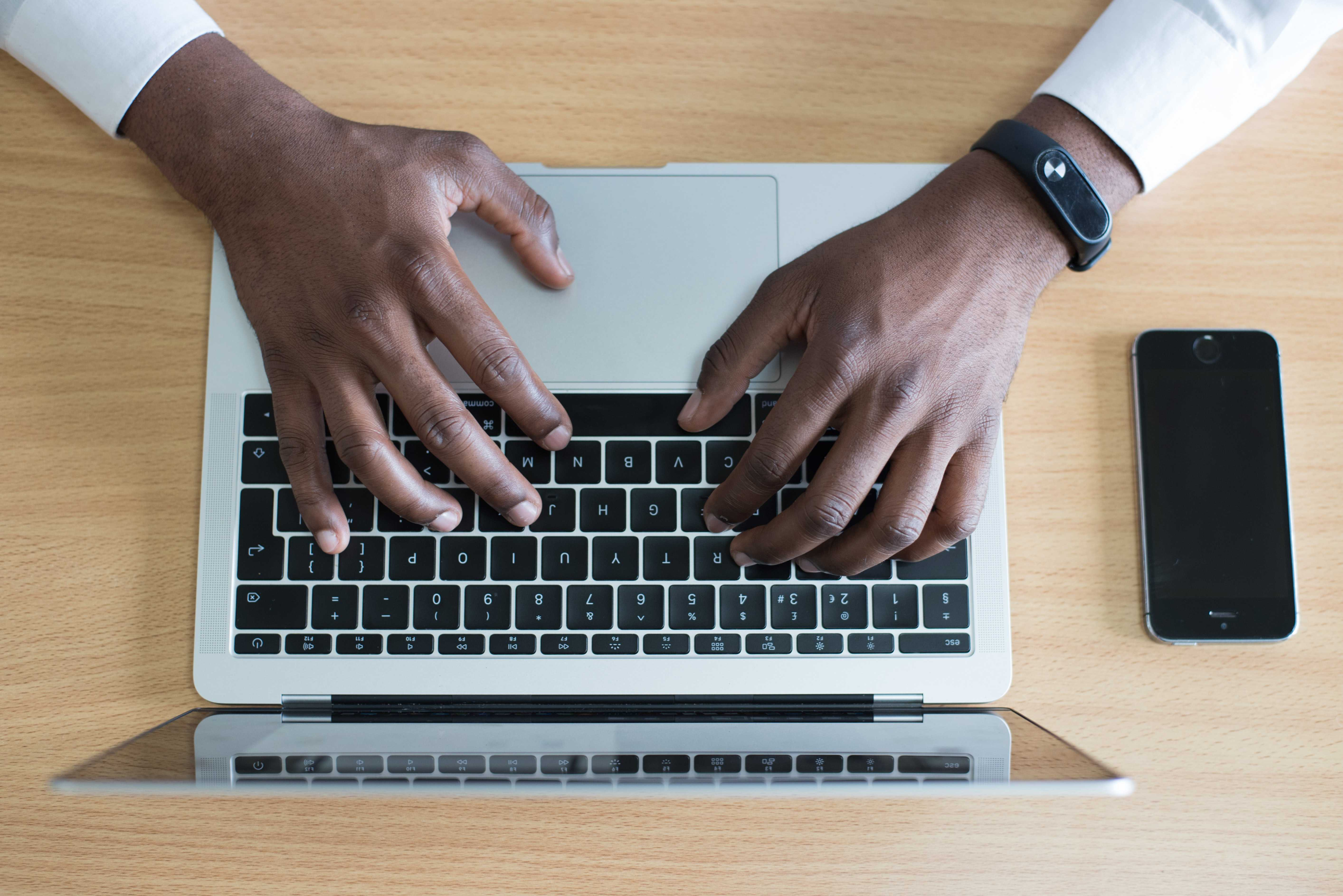 Black person's hands using a laptop
