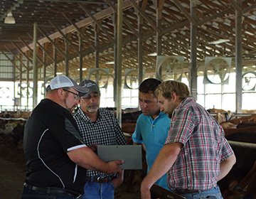 4 men in a barn around a computer
