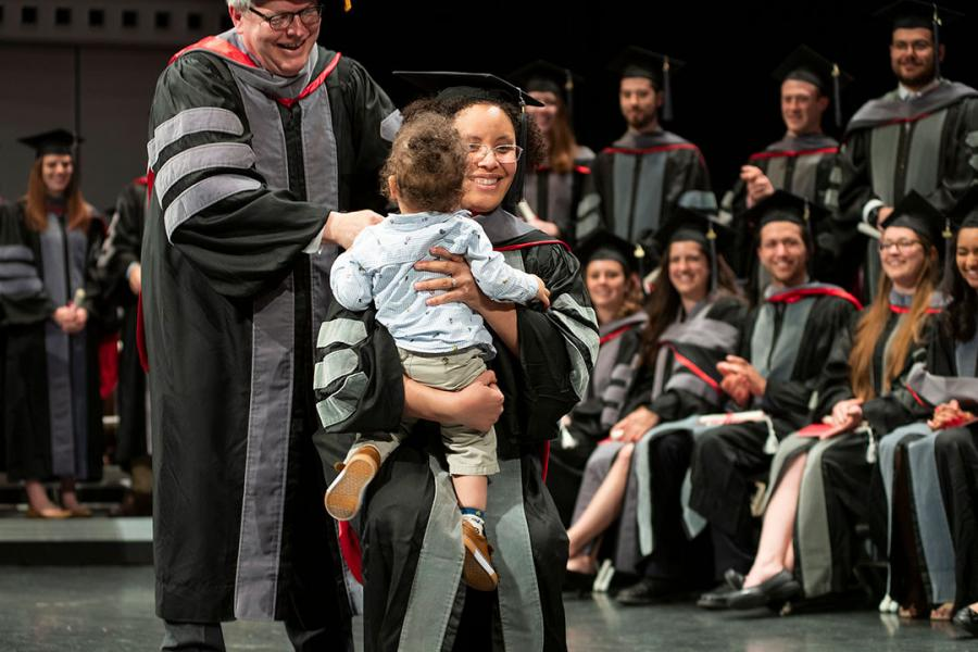 A graduate holding a baby receives her hood from Dean Warnick
