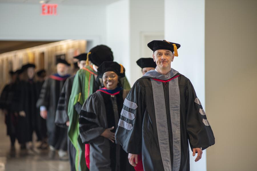 A line of faculty walking into the MPH 2019 hooding ceremony