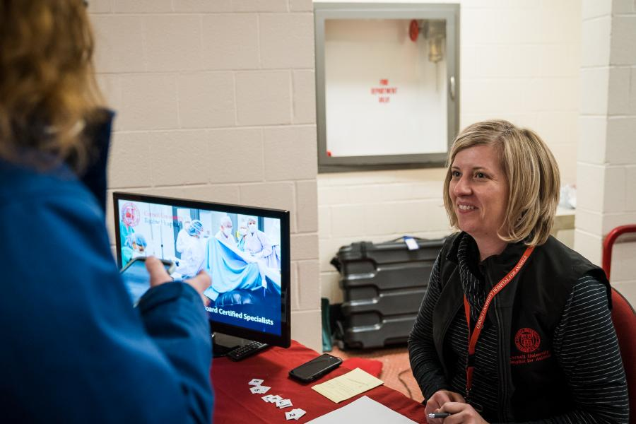 Hospital staff member checks in a tour participant.