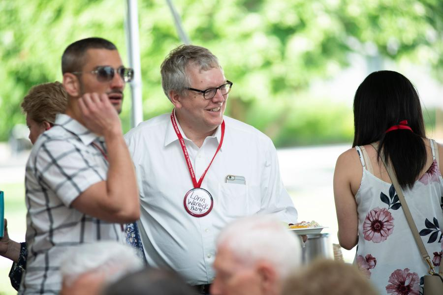 Dean Warnick smiles with guests at the CVM bar-be-que