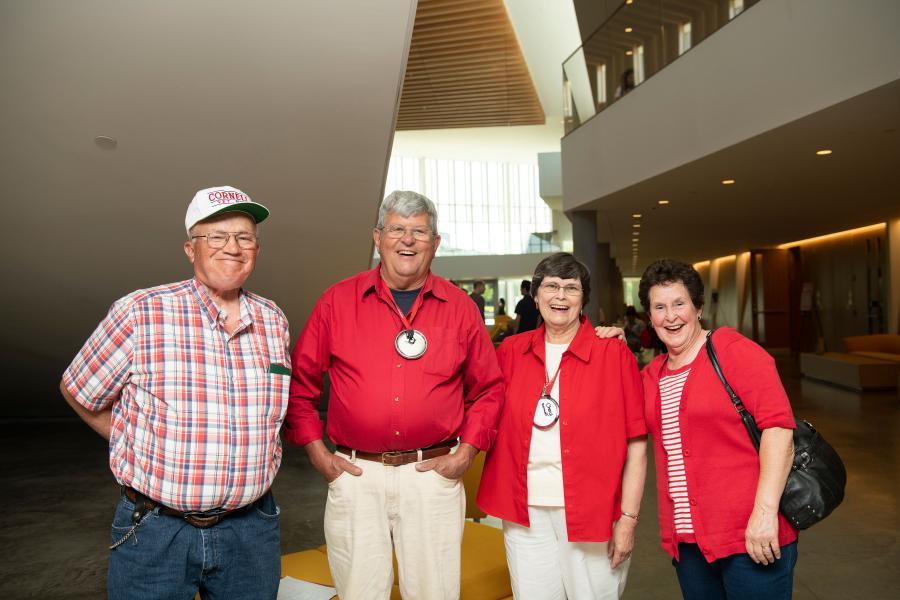 Four alumni pose for the camera in the CVM atrium