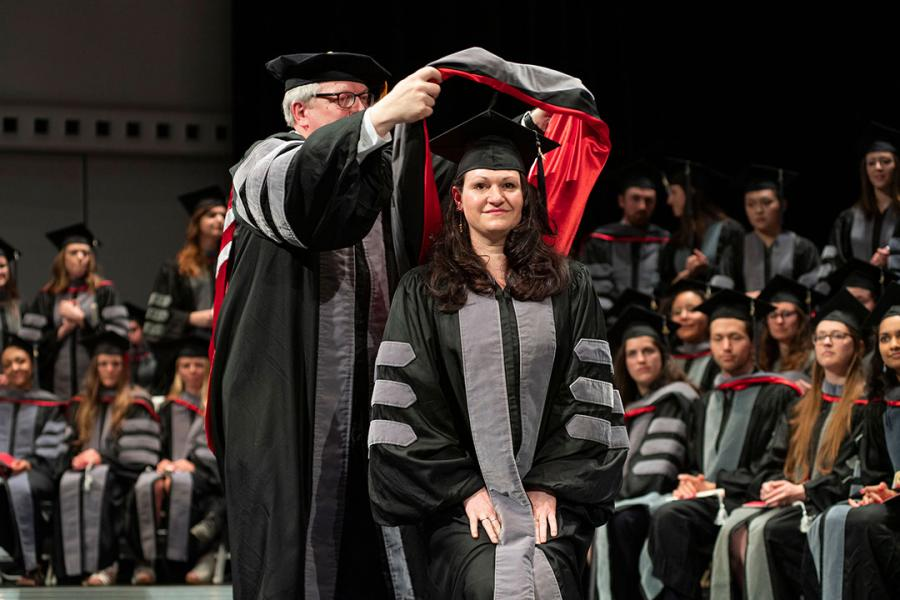 A student receives her hood from Dean Warnick