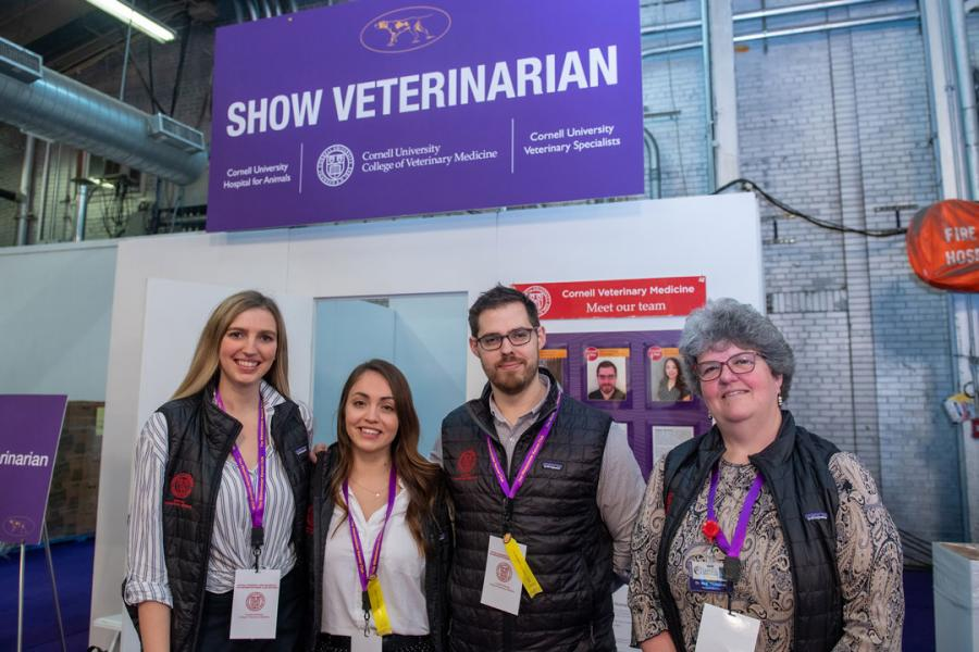 Students and clinicians pose in front of the vet booth