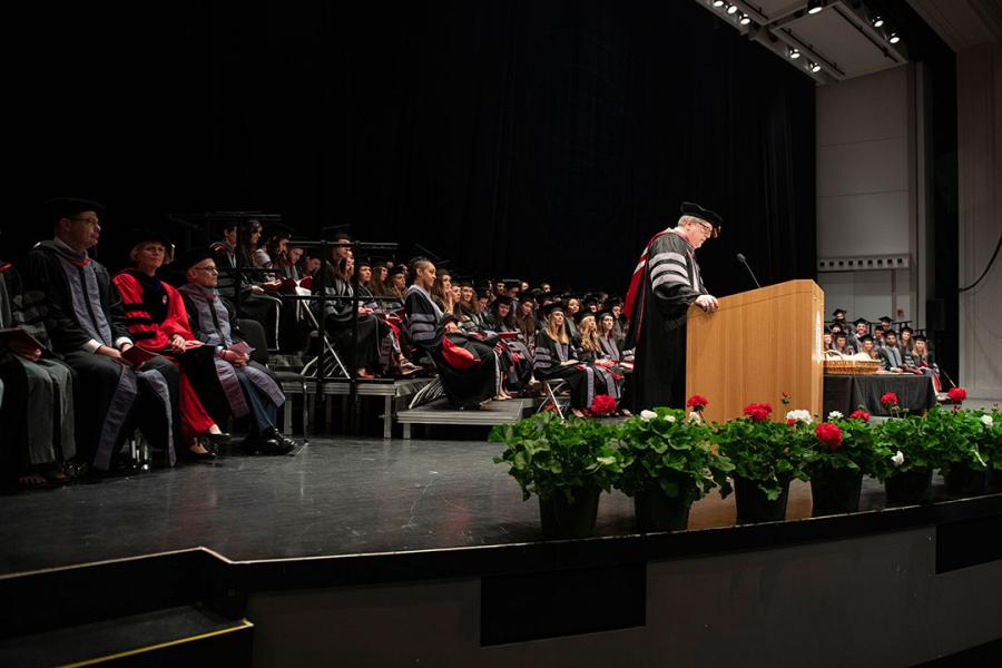 Dean Warnick at podium during hooding ceremony