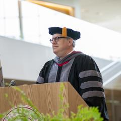 Dean Warnick at a podium during the MPH hooding ceremony