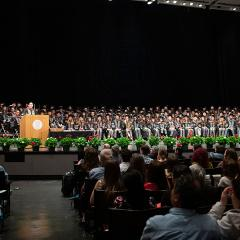 Keynote speaker talking to the crowd at 2019 hooding ceremony