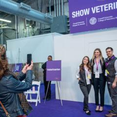 A person takes a cell phone picture of the students and clinicians in front of the veterinarian tent