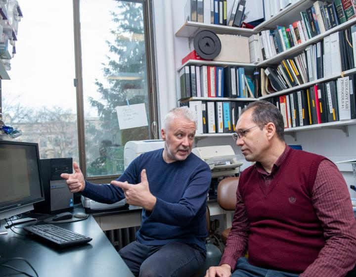 Two men in a faculty office examining a computer screen