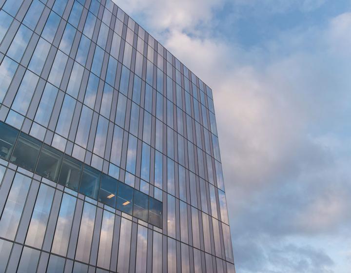 Exterior of Schurman Hall's glass walls against a blue sky