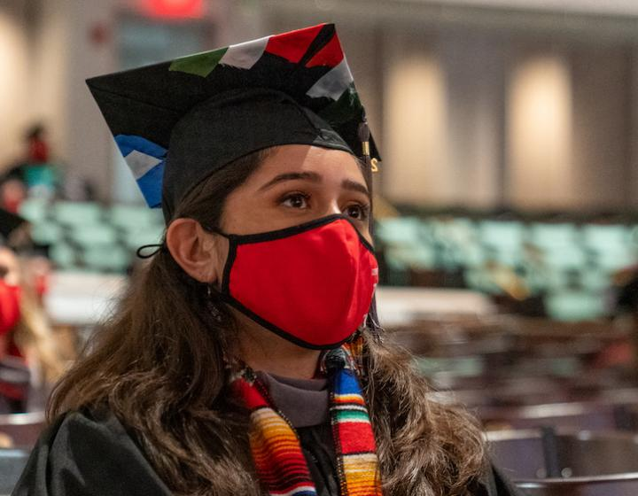 A veterinary student in a cap and gown with a mask on listens to the keynote speaker at the college's send-off ceremony