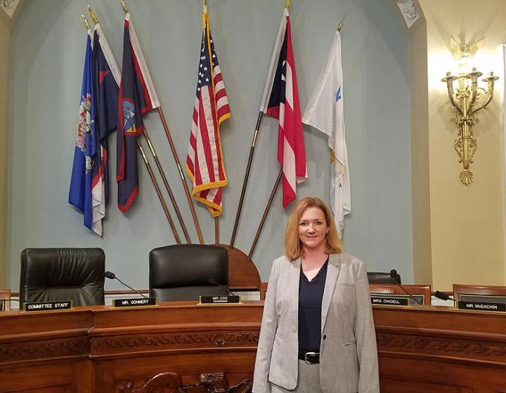 Krysten Schuler standing inside the House of Representatives, with flags and a giant desk behind her
