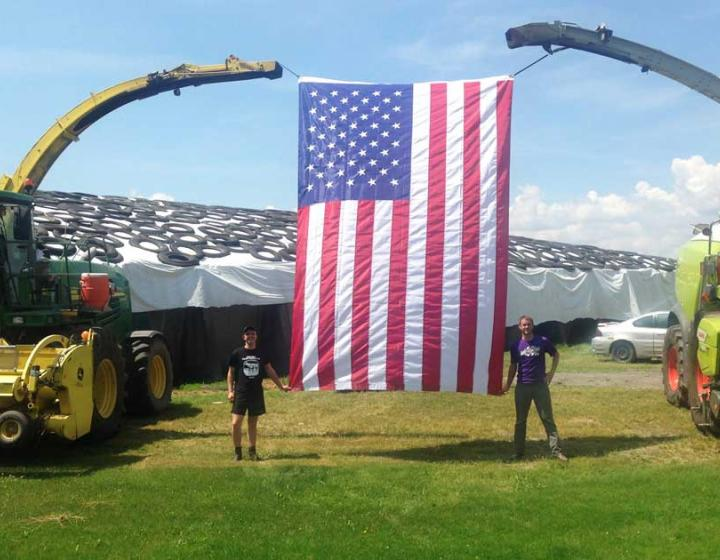 Two people standing beneath an enormous American flag that is hung between two tractors