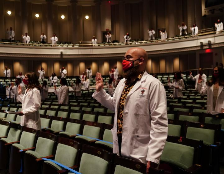 Veterinary students in white coats take the Veterinarian's Oath in Bailey Hall
