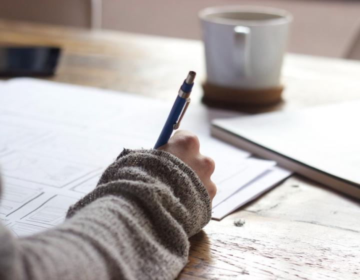 Stock image of a person in a sweater at a writing desk, with papers and a mug before them