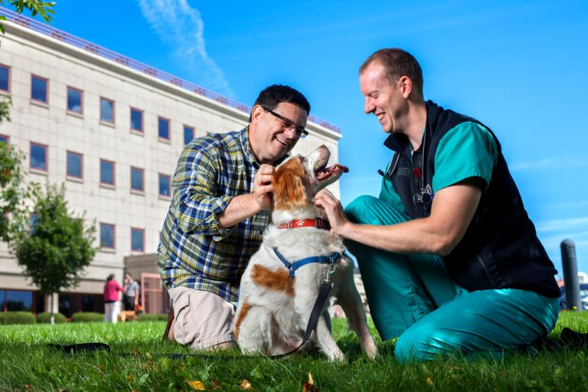 Dr. Chris Frye and male client happily pet a dog in front of Cornell's Hospital for Animals
