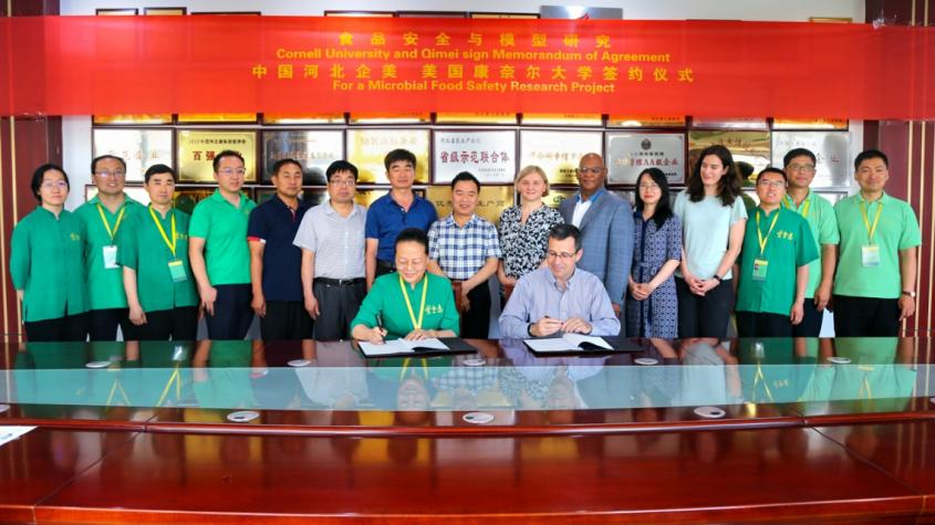 Yuqi Zhao, president of Qimei, left, and Martin Wiedmann, sign an agreement to collaborate on microbial food safety research while participants look on