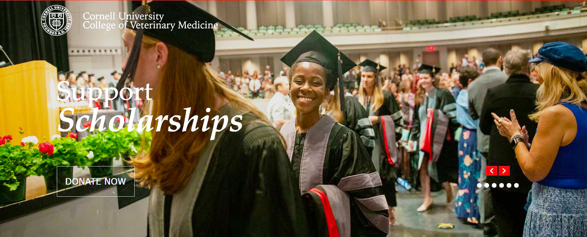 "A screenshot of the CVM Giving page, displaying the words ""Support Scholarships"" over a photo of a student smiling during the 2018 hooding ceremony"